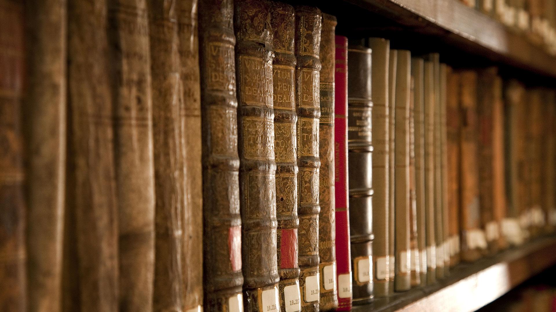 Närbild på staplade böcker i bokhylla