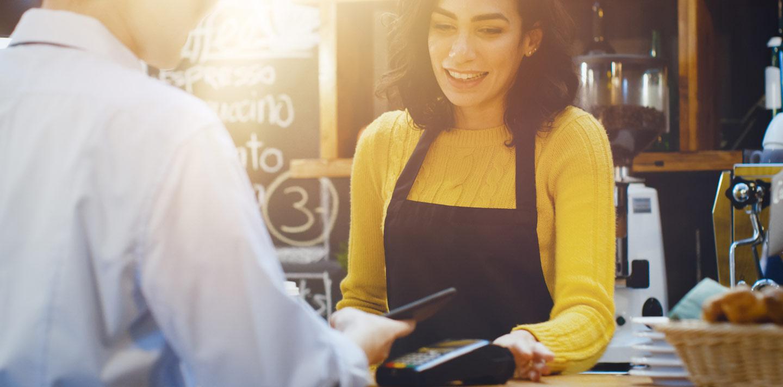 Betalande kund och kassörska i cafémiljö